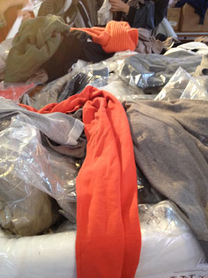 Piles and piles of plastic bagged shirts, sweaters, and tanks stacked inside