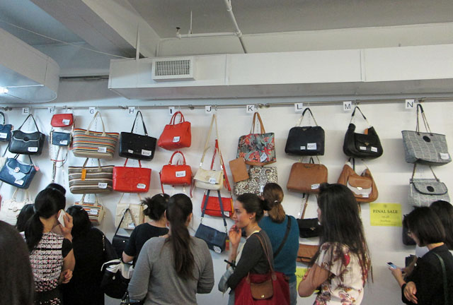 Large wall full of handbag samples priced from $98-$250